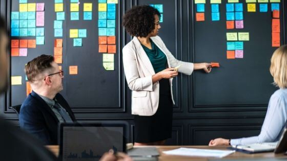 a multi-cultured female entrepreneur standing up in front of a black accent wall with colorful post-it-notes leading a meeting with staff members seated