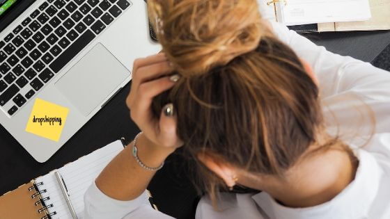Business woman stressed out holding her head on her hand looking down in front of a laptop with a written yellow post-it-note that reads dropshipping