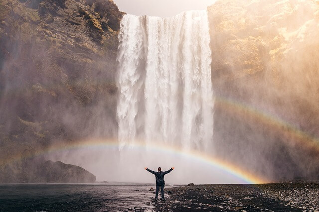 a man standing in water looking at a small arched rainbow in between him and a waterfall inspired by more freedom