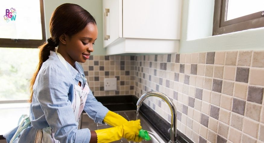young girl washing the dishes in the sink to earn some money