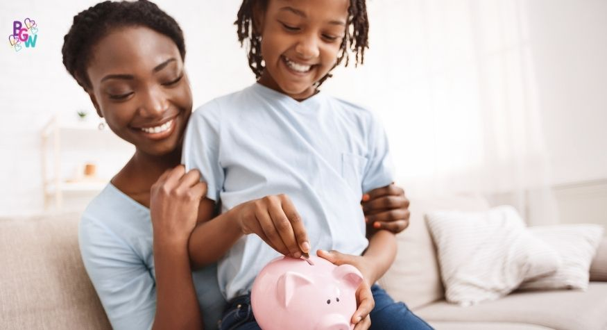 smilingyoung girl putting a coin into a piggy bank while her mother smiles next to her