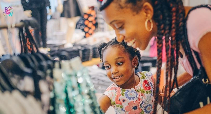young girl shopping for clothes with her mother